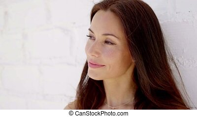 Close up of woman with brown hair smiling while standing...