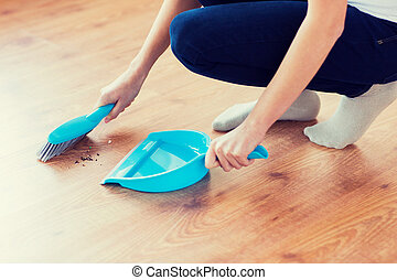 close up of woman with brush and dustpan sweeping - people,...
