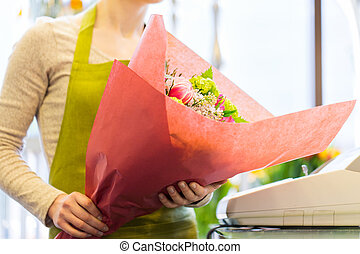 close up of woman with bunch at flower shop