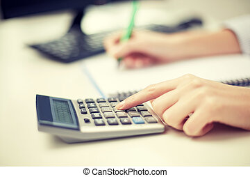 close up of woman with calculator taking notes