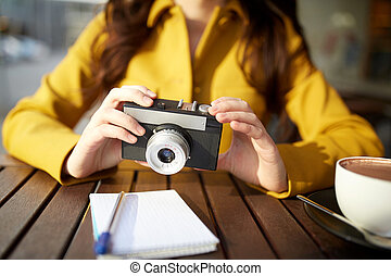 close up of woman with camera at city cafe
