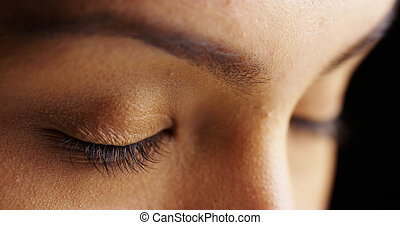 Close up of woman with closed eyes on black background