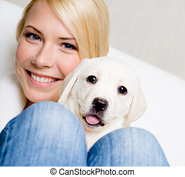 Close up of woman with cute puppy on her knees
