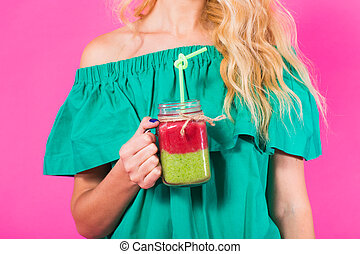 Close up of woman with green smoothie on pink background
