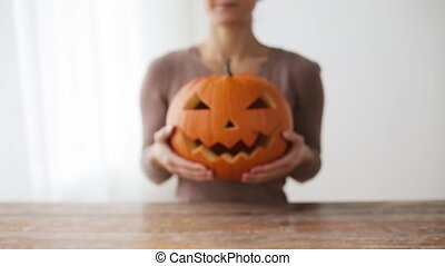 close up of woman with halloween pumpkin at home