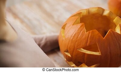 close up of woman with halloween pumpkin at home -...