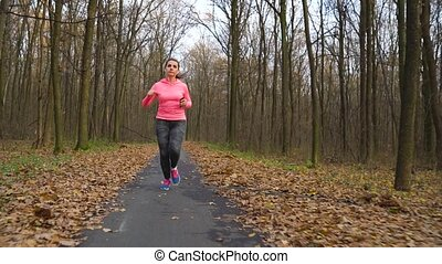 Close up of woman with headphones and smartphone running...