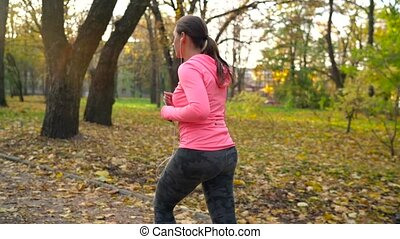 Close up of woman with headphones and smartphone running through an autumn park at sunset