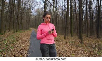 Close up of woman with headphones and smartphone chooses the music and running through an autumn forest at sunset. Slow motion