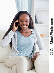 Close up of woman with her mobile phone on the sofa