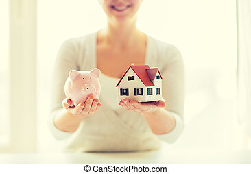 close up of woman with house model and piggy bank