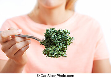 Close Up Of Woman With Kale On Fork