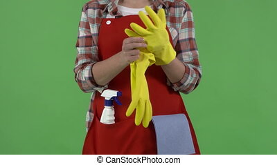 Close-up of woman with rag and cleanser spray ready for cleaning green screen