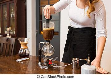 close up of woman with siphon coffee maker at shop -...