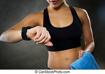 close up of woman with smartwatch and towel in gym - sport, ...
