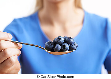 Close Up Of Woman With Spoonful Of Blueberries