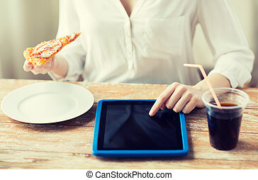 close up of woman with tablet pc having dinner
