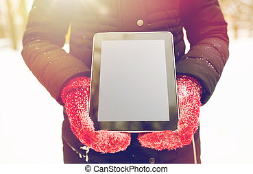 close up of woman with tablet pc in winter