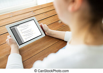 close up of woman with tablet pc on wooden table