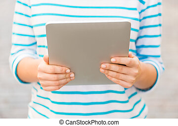 close up of woman with tablet pc outdoors