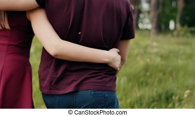 Close-up of womans and mans arms round each other in an embrace. Couple walking in nature. Slow mo, steadicam shot