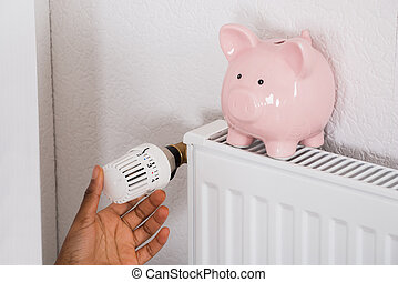 Woman's Hand Adjusting Thermostat With Piggy Bank On Radiator