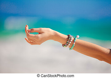 Close-up of woman's hand background the turquoise sea