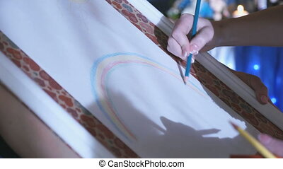 Close-up of woman's hand drawing rainbow on easel - Close-up...
