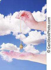 Close up of woman's hand holding a pendulum in motion over her palm. Blue sky and white clouds in background.