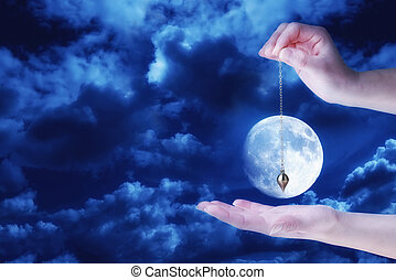 Close up of woman's hand holding a pendulum over her palm. Cloudy sky and full moon at night in background.
