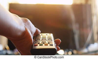 Close up of woman's hand with a television remote control at sunset time