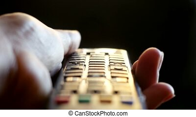 Close up of woman's hand with a television remote control changing channels at sunset time. 3840x2160