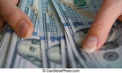 Close-up of woman's hands counting hundred dollar bills