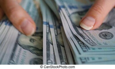 Close-up of woman's hands counting hundred dollar bills. Slow motion