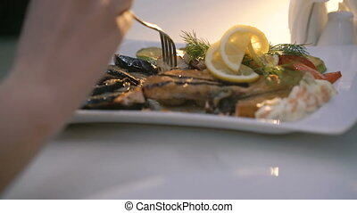 Close up of woman's hands cutting dish on plate at table in restaurant