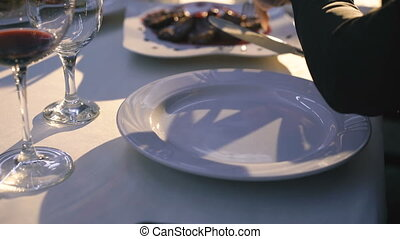 Close up of woman's hands cutting fish and chop on a plate in restaurant 4K