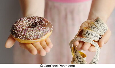 Close-up of woman's hands holding a donut and a measuring tape