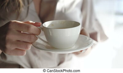 Close up of woman's hands holding white saucer and drinking