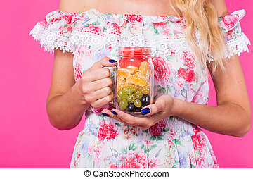 Close up of woman's hands holds fruit jar on pink background