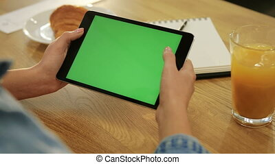 Close-up of woman's hands scrolling down page on tablet with green screen in the cafe. Close-up. Chroma key. Greenscreen. social network