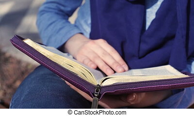 Close-up of woman's hands while reading the Bible outside