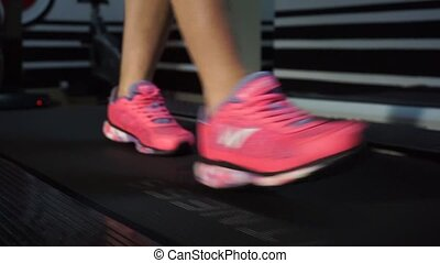 Close up of woman's legs on a treadmill in the gym.
