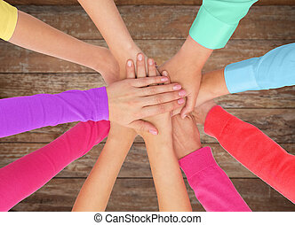 close up of women hands on top in rainbow clothes