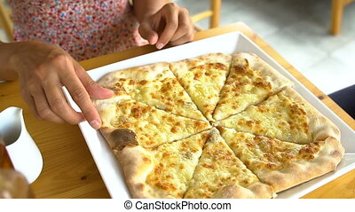 Close up of women taking cheese pizza slices from small plate