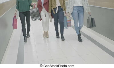 Close up of women wearing different clothing styles and shoes walking in mall holding shopping bags