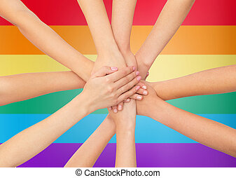 close up of women with hands on top over rainbow