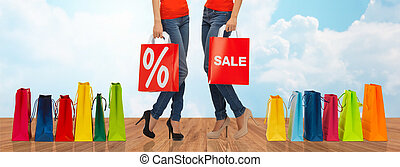 close up of women with sale sign on shopping bag