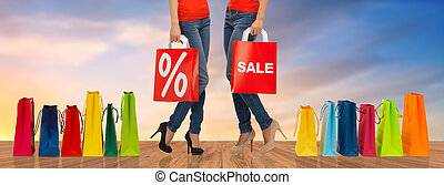 close up of women with sale sign on shopping bags
