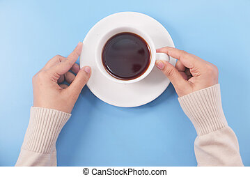 hand holding tea cup on light blue background