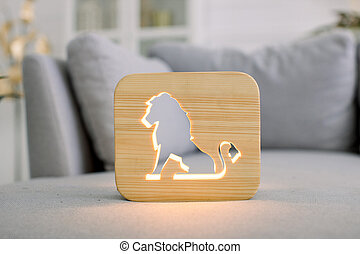 Close up of wooden night lamp with lion cut out picture, at stylish light home living room interior, on gray modern sofa. Home decor and accessories